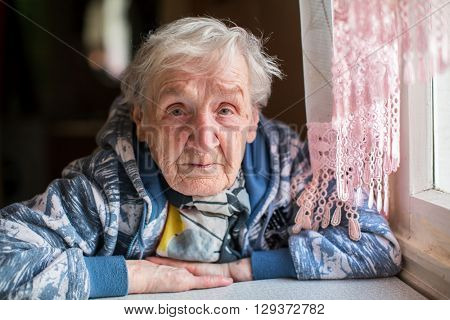 Sad elderly woman portrait at the table.