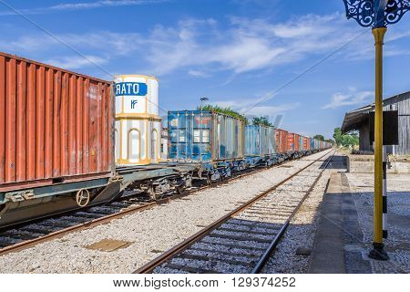 Crato, Portugal. July 2, 2015: A freight train from Comboios de Portugal (Portuguese Trains) passing by a deactivated Railroad Station in the interior south of Portugal.