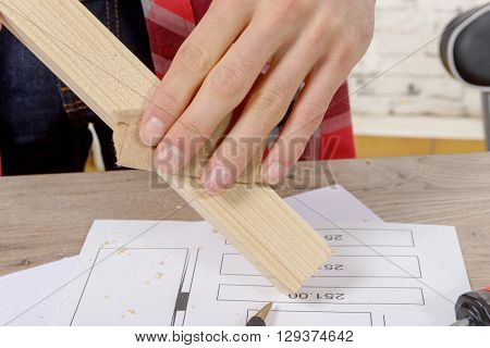 close up of hand of carpenter sanding a wooden board
