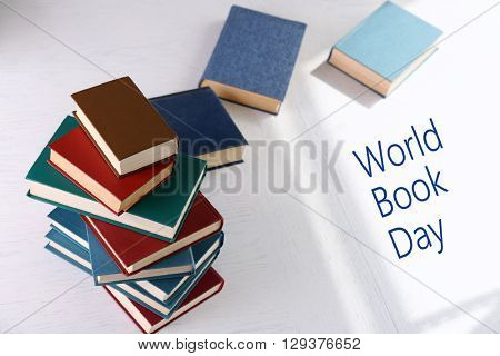 Stack of books on light surface background. World Book Day poster
