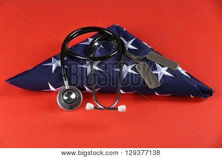 Stethoscope with tokens and stars of USA flag on red background