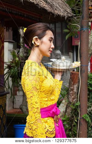 UBUD INDONESIA - MARCH 2 2016: Young woman with silver plate on palm during the celebration before Nyepi (Balinese Day of Silence) on March 2 2016 in Ubud Indonesia.