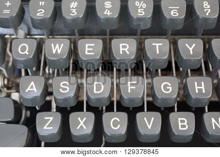 Detail view of the keys on a portable metal typewriter circa 1970. Focus is on QWERTY. May be used to symbolize journalism or creativity or an antiquated method of communication.