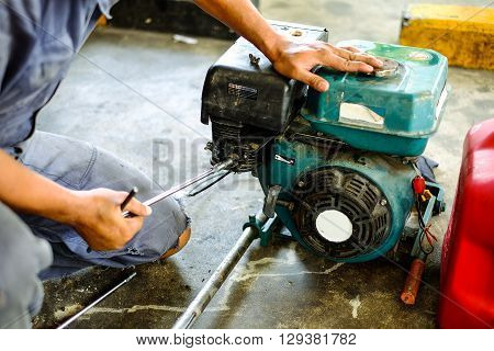 mechanic repairing Diesel engine of Thai traditional long tail boat