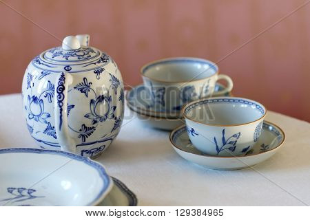 Coffee set made of white and blue porcelain on a table with linen cloth and a pink wall behind. Short depth of focus
