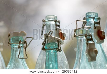 Group of back lit blue and transparent old fashioned empty glass bottles in a window closeup