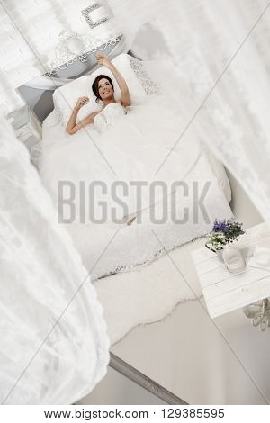 Beautiful happy bride lying on bed in white bedroom, making selfie by mobilephone.