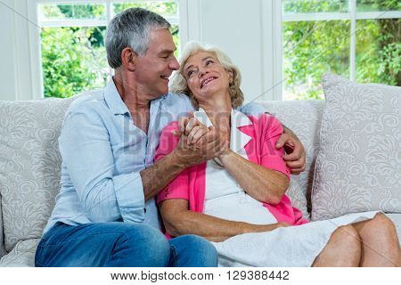 Loving senior couple looking at each other on sofa in living room