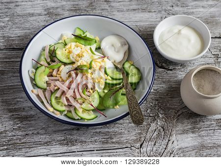 Salad with smoked turkey cucumber and boiled egg on a light rustic wooden background. Healthy food