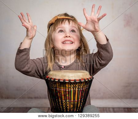 cute little girl with headband playing drum on the floor