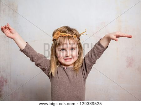 pretty little girl with headband dancing with hands up in motion