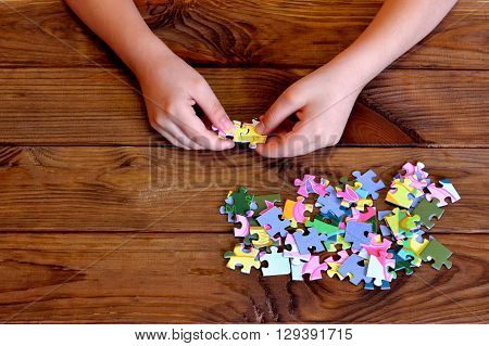 Child working on jigsaw puzzle. Child holding a puzzle in hands. Group of jigsaw puzzles on wooden table
