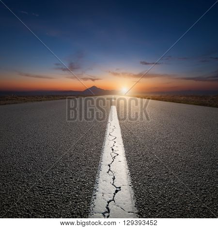 Empty highway leading to the mountains through the desert against the rising sun at beautiful sunrise.