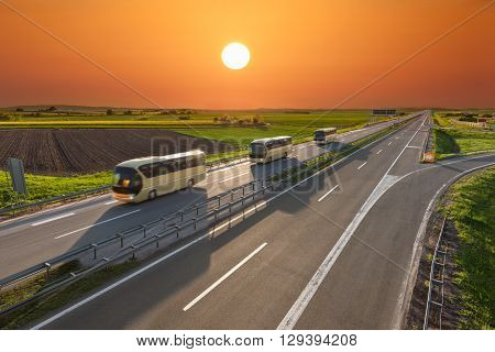 Modern golden buses driving in blurred motion on the freeway at beautiful sunset. Transport and travel scene on the motorway near Belgrade Serbia.