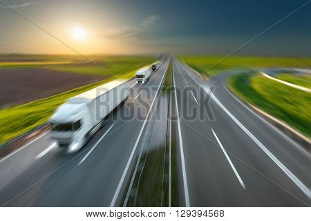 Three new trucks in a row driving fast towards the sun. Speed blurred motion drive on the freeway. Freight scene on the motorway near Belgrade Serbia. Speed concept.