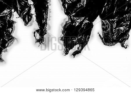 Ripped black plastic cover on white background