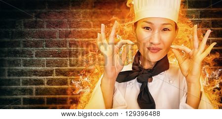 Closeup of a smiling female cook gesturing okay sign against image of a wall