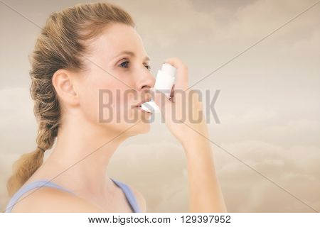 Woman using inhaler for asthma against maroon background