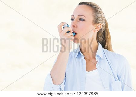 Pretty blonde using an asthma inhaler against yellow background