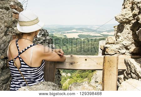 Young caucasian tourist woman in a sailor outfit on the ruins of the castle Cachtice. Travelling theme.