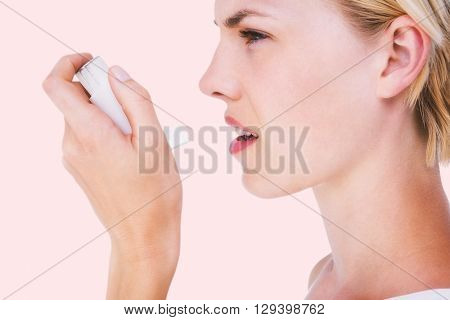 Asthmatic pretty blonde woman using inhaler against beige background