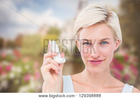 Pretty woman holding inhaler smiling at camera against canal in amsterdam