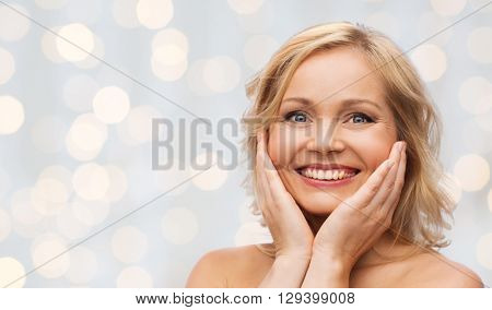 beauty, people and skincare concept - smiling woman with bare shoulders touching face over holidays lights background