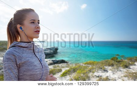 fitness, sport, people, technology and lifestyle concept - happy woman running and listening to music in earphones