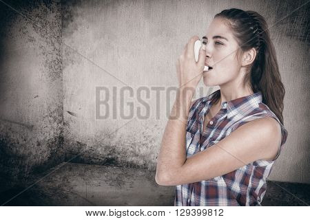 Woman having asthma using the asthma inhaler against image of room corner