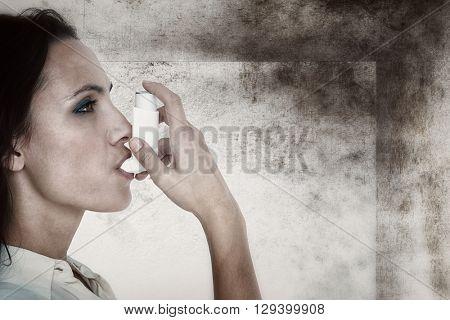Asthmatic brunette using her inhaler against image of room corner