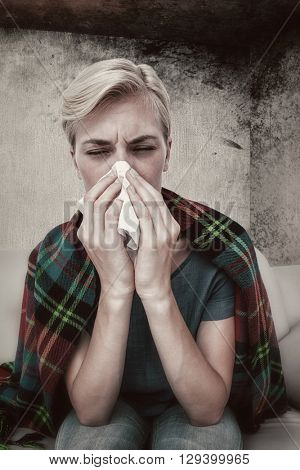 Sick blonde woman blowing her nose against image of room corner