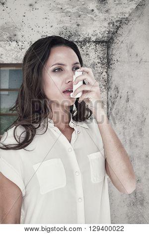 Asthmatic brunette using her inhaler against image of a room corner