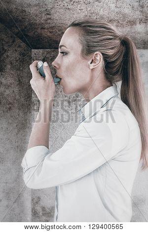Beautiful blonde using an asthma inhaler against image of room corner