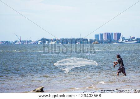 Menumbok,Sabah-Nov 13,2015:Fisherman throwing fishing net during sunny day at Menumbok,Sabah,Borneo.
