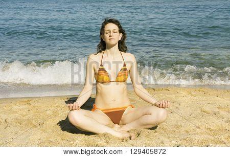 Young European woman meditating on sea beach.