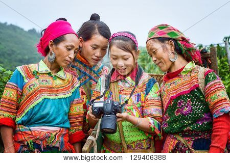 Ha Giang, Vietnam - September 23rd, 2015: Ethnic watching camera image with gentle smile, colorful clothing, they very happy to see their image after hours hard labor mountains in Ha Giang, Vietnam