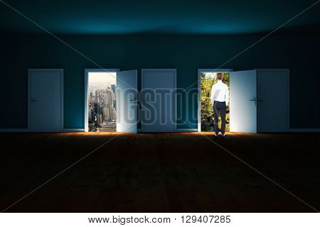 Rear view of businessman with hands in pockets against doors opening in dark room to show sky