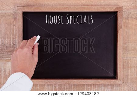 House specials message against view of hand writing on blackboard