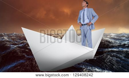 Full length of businessman with hands on hips against paper boat floating on the sea