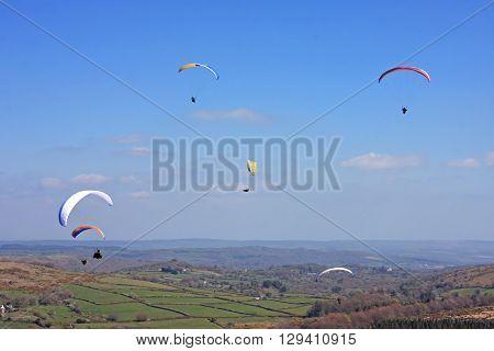 Paragliders flying high above Dartmoor in Devon