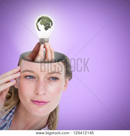 Hand holding environmental light bulb against purple background