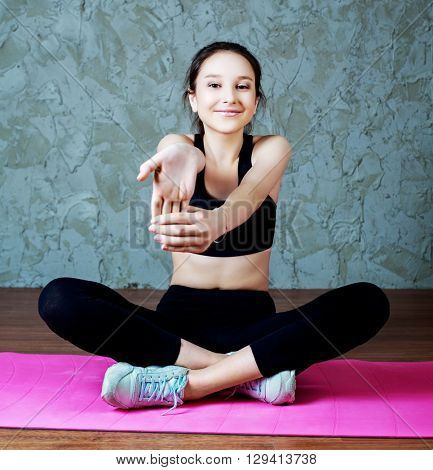 young sporty woman stretching the musles of her arms