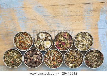 collection of nine herbal blend Chinese tea in round metal cans, top view against painted grunge wood with a copy space