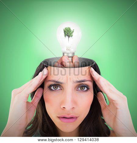 Hand holding environmental light bulb against green background