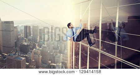 Businessman pulling a rope with effort against image of a city landscape on a sunny day
