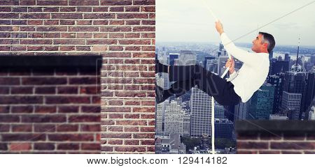Businessman pulling rope while sitting on cube against red brick wall