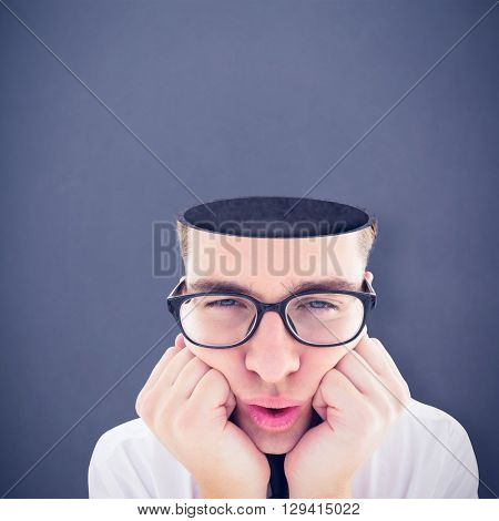 Geeky hipster falling asleep on hands against grey background
