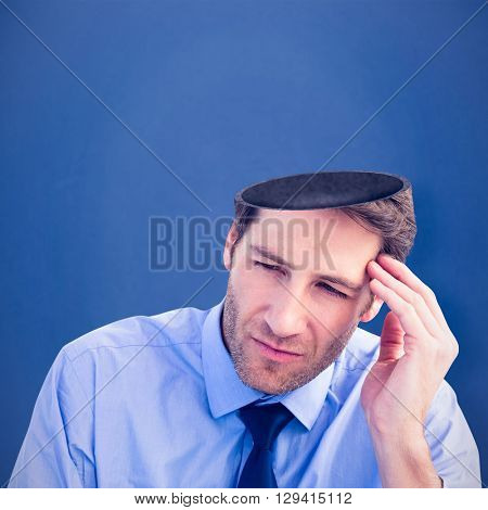 Stressed businessman holding his head against blue background