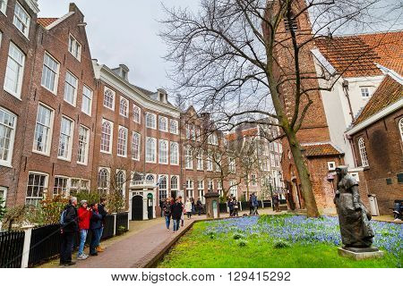 Amsterdam, Netherlands - March 31, 2016: Begijnhof courtyard with nun statue, historic houses and tourists in Amsterdam, Netherlands