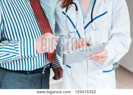 Close-up  of doctor and patient hands holding papers with prescription. Healthcare concept.